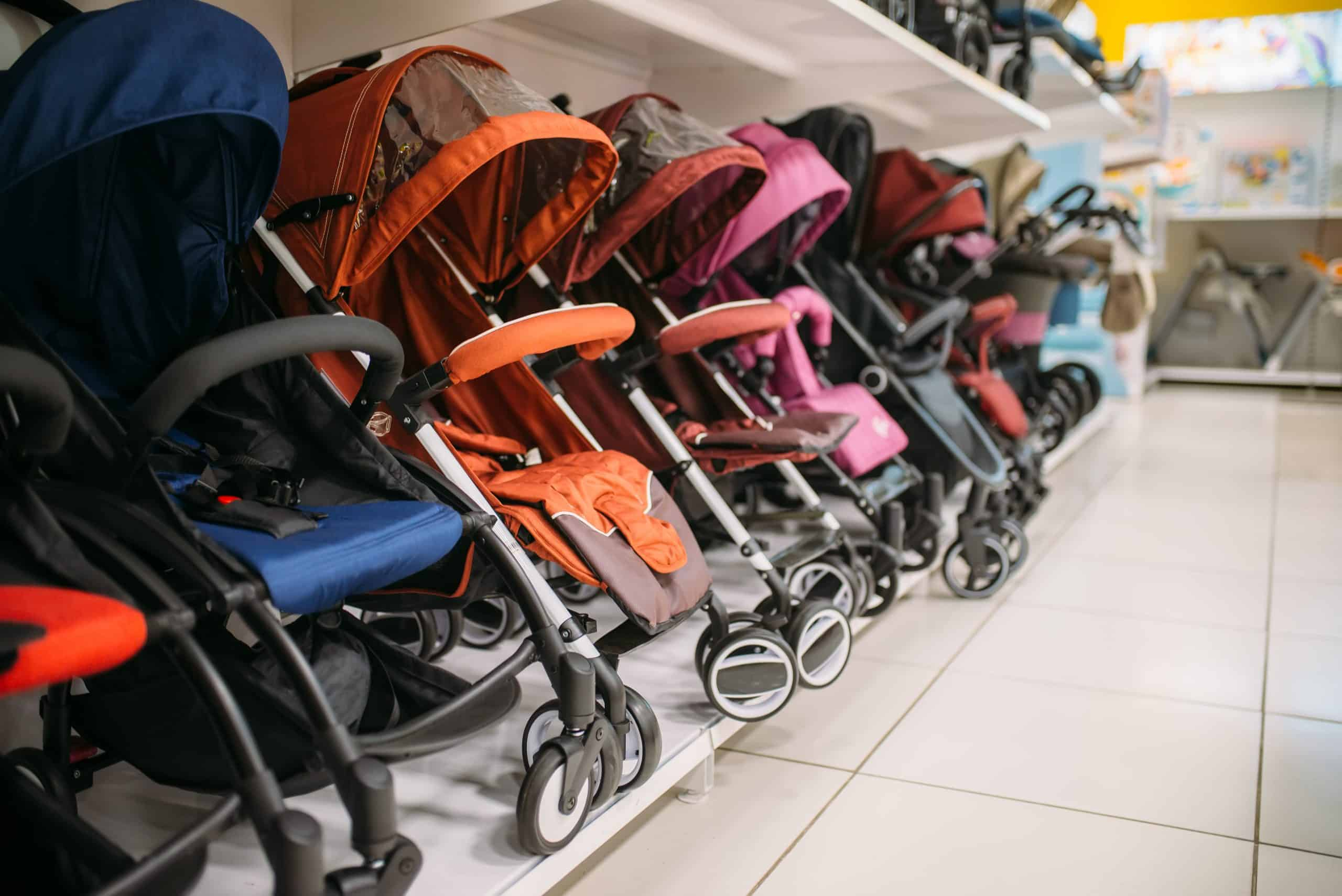An image showing a row of 3 wheel and 4 wheel strollers in a store